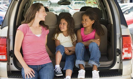 mother and two girls sitting in back of van