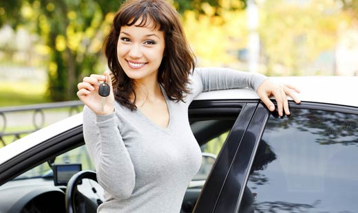 smiling woman holding car keys up